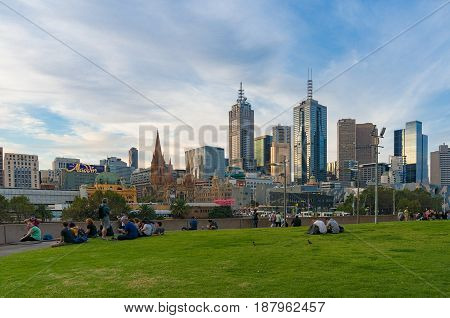 People Relaxing On Green Lawn With View Of Melbourne Cbd