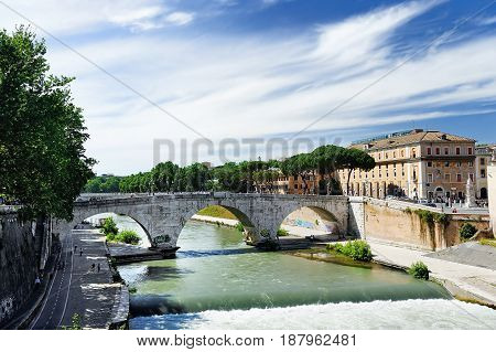 View Of Tiber Island Across Tiber River With Ancient Roman Stone Bridge Pons Cestius In Rome, Italy