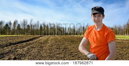 Happy Young smiling farmer in orange t-shirt standing at the background of plowed field in springtime