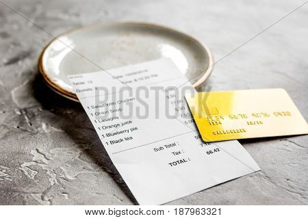 restaurant bill, credit card and plate on stone table background