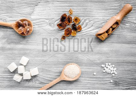 lumps of sugar in spoons on gray kitchen table background top view