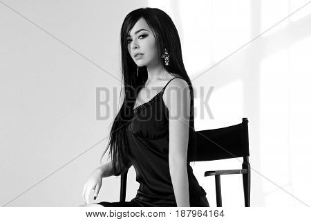 Young stunning and sexy tanned brunette woman with long straight hair wearing black micro tunic dress and sitting in high directors chair. Sun light with beautiful shadows. Fashion portrait.
