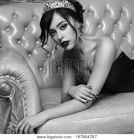 Sensual stunning young brunette woman in red slit mermeaid dress lying on sofa. Sexy girl in crown and cross earings. Top view. Fashion portrait.