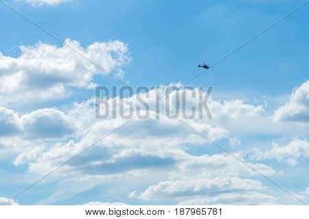 Blue Sky With Sculpted Clouds On The Background With Real Tinny Helicopter Flying On The Left Side