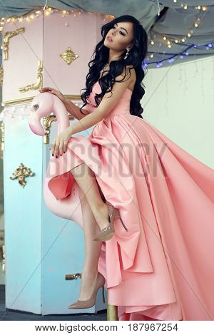 Fashion vogue style portrait. Elegant lady with brunette curly hair in pink ball gown at carousel.