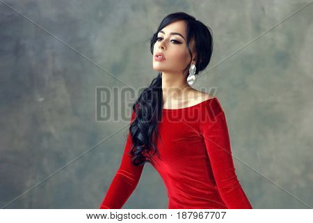 Fashion portrait of stylish brunette girl wearing red velvet dress Woman with ponytail hair wearing earrings. Model sitting on wooden chair