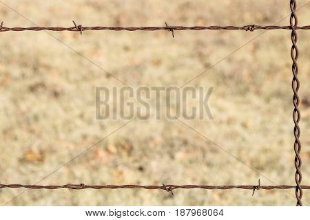 A rusty barbed wire fence frames a blurred brown country field. Can be used as background or border.