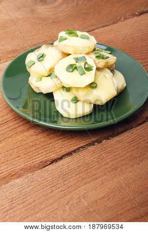 Appetizer of potatoes cheese and green onions on wooden background. There is room for text