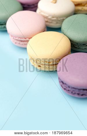 Picture of a lot of sweet colorful macaroons on blue table background.