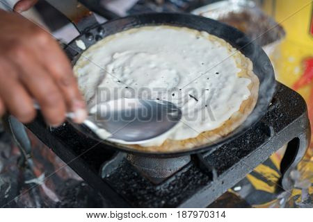 Close Up Of Dosa Cooking On Skillet