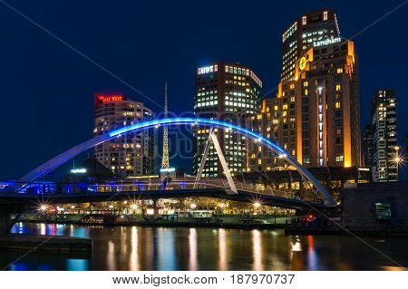 Southbank Pedestrian Bridge Across Yarra River And Melbourne Cityscape At Night