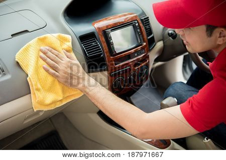 A man cleaning car interior - car detailing and valeting concept