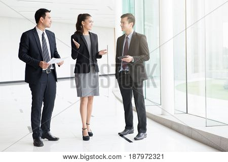 Business people talking and discussing work in building hallway