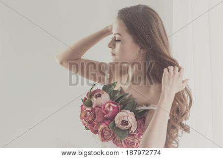 Sweet girl in her underwear adjusts her hair. Bra of flowers. Spring mood. Soft focus. Close-up portrait