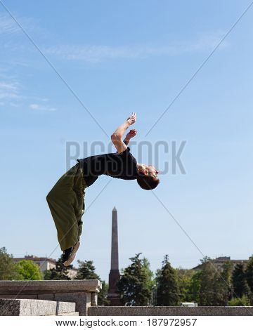 Young man doing a back flip in the background obelisk. Parkour in the urban space. Sport in the city. Sport activity.