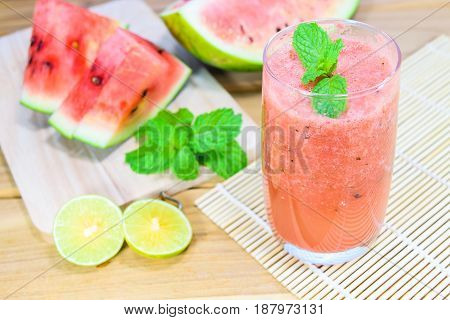 Watermelon smoothies with lime and mint on wooden background