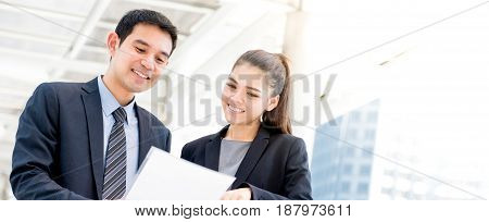 Asian businessman and businesswoman discussing document panoramic banner