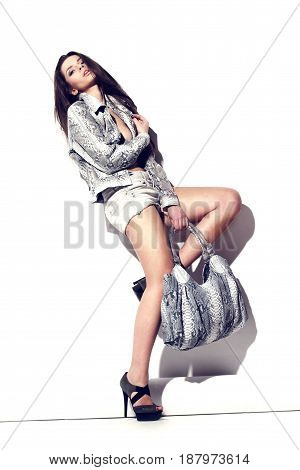 young beautiful fashion female model posing in reptile leather vest with leather bag