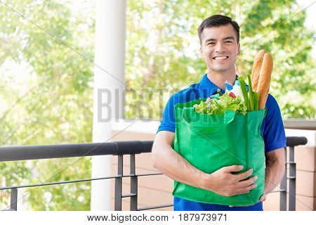 Smiling delivery man holding recycle grocery shopping bag with food inside