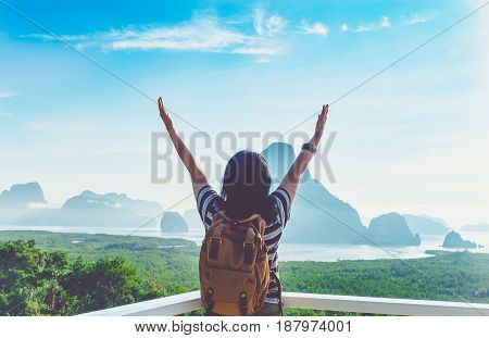 Happy young traveler woman backpacker raised arm up to sky enjoying a beautiful of nature at top of mountain view point and seaFreedom wanderlustKhao Samed Nang Chee ViewpointPhang NgaThailand.