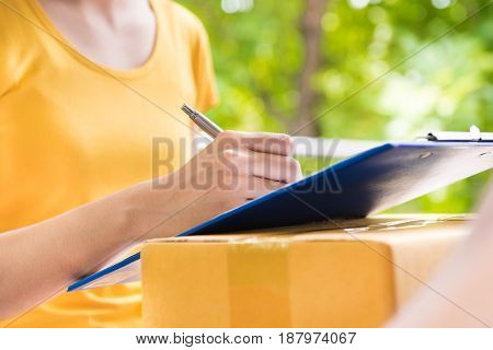 Young woman signing document while receiving package - courier and delivery service concepts