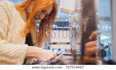 The red-haired girl in glasses choosing an outfit in the women's clothing store