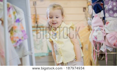 Sweet girl in a new summer suit, looking at myself in the mirror in the children's clothing store