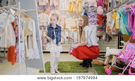 Shopping for kids - a little girl tries on a denim jacket in front of a mirror