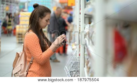 girl buys a jam in a store or supermarket