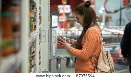 Girl buys pickled tomatoes in store or supermarket