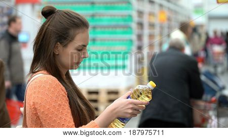 Woman buys sunflower oil in the store or supermarket