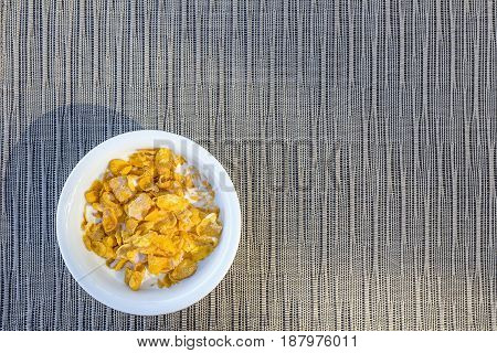 Top view image of corn flakes with milk in white bowl on weave mat background. Place for text.
