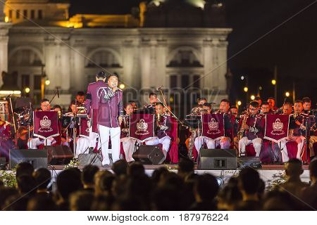 Bangkok Thailand May 20 2017; Singer of Thai Police Band singing with orchestra band for people at the ground Equestrian Statue of King Chulalongkorn Blurred Ananda Samakhom Throne Hall background