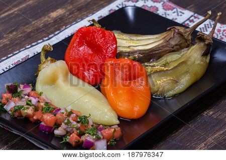 Roasted vegetables - eggplant and pepper with tomato salsa in black plate close up