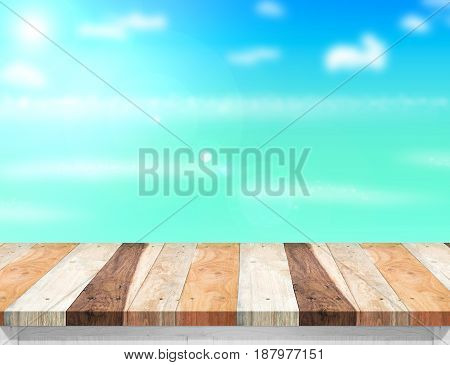 Wood table top with blurred seasun and beach at background Mock up template for display or montage of your product Summer holiday concept.