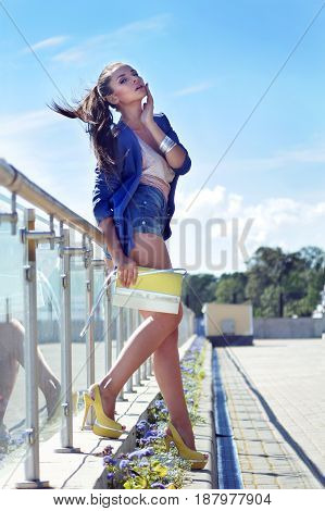 full length outdoor portrait of young stylish woman standing near fence