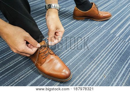 close up businessman lace his shoes in office