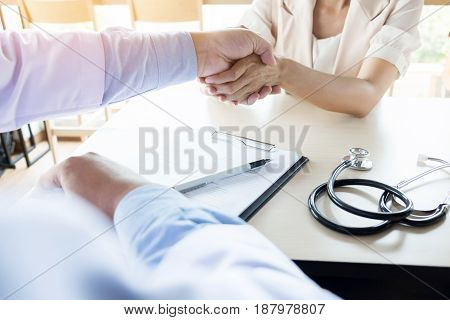Doctor Shakes Hands At Medical Office With Patient, Wearing Glasses, Stethoscope And Lab Coat.