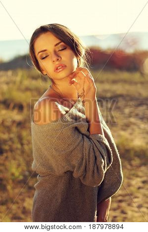 young beautiful sensual tender woman posing in autumn fields with closed eyes