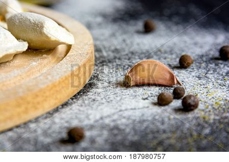 Close up single garlic clove, pepper seeds and flour on dark wooden table