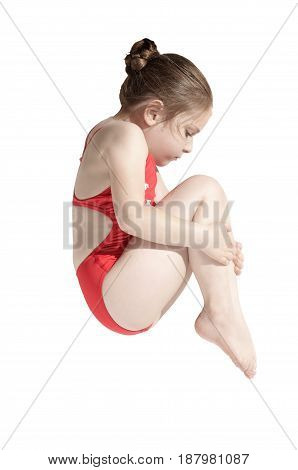 Little caucasian female diver (6 years old) jumping in diving pose  tucked his knees to his chin on white background.