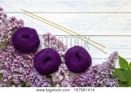 Purple tangles of yarn and knitting needles on a wooden background. Top view. Around the flowers of lilac.