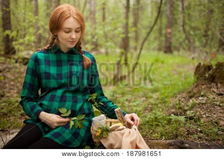 pregnant redhead girl in the forest on a picnic