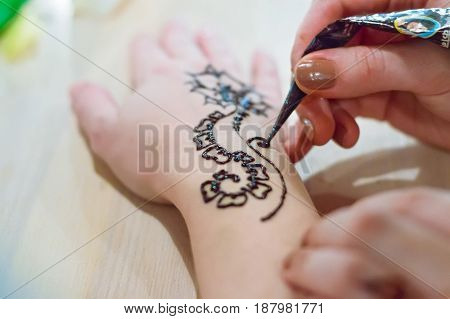 Closeup hands of woman making henna tattoo on hand