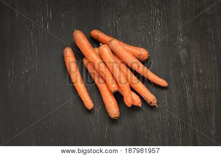 Carrots on black wooden background. Overhead shot