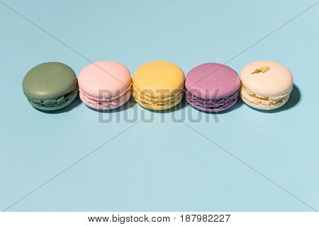 Image of five sweet colorful macaroons on blue table background.