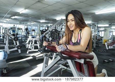 Fitness woman in training showing exercises with building muscles in gym soft focus