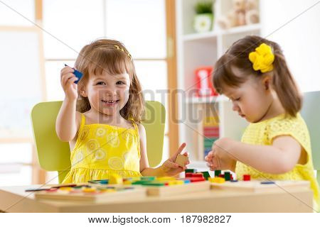 Children playing with developmental toys at home or kindergarten or playschool