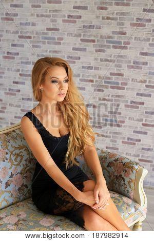 Sexy Beautiful Girl In Black Dress On Sofa.