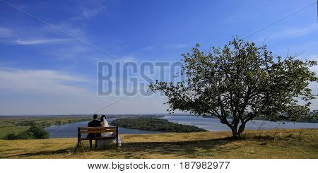 Young Wedding Romantic Couple Sitting On Wooden Bench Outdoor On Natural Background